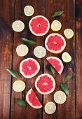 Ripe slices lemon and grapefruit on wooden background
