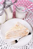 Napoleon cake with milk on table close-up