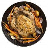 Roast chicken dinner on black plate, isolated on white.  Top view.
