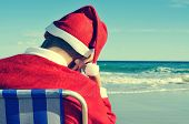 santa claus taking a nap in a beach chair on the beach