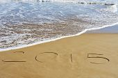 the number 2015, as the new year, written in the sand of a beach