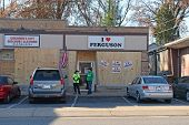 FERGUSON, MO/USA - NOVEMBER 25, 2014: Ferguson business owners show support for city in the aftermath of riots in front of boarded up windows.