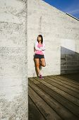 Female Athlete Leaning Against Wall With Arms Crossed