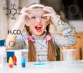 happy little girl with flasks for chemistry