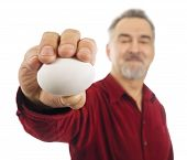 Mature Man Holds A Blank White Egg In His Outstretched Hand.
