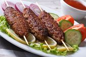 Three Kebab Of Minced Meat And Fresh Vegetables