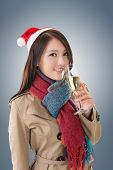 Smiling Asian woman hold a  glass of champagne and look at you in a Christmas party, closeup portrait.