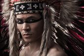 image of headdress  - Naked indian strong man with traditional native american make up and headdress looking at the camera - JPG