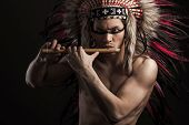 Portrait of the indian strong man posing with traditional native american make up. Playing flute