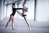 Two young slim gymnast women dancing on urban background. Bright white colors.