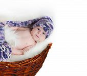 Newborn baby lies in basket in a multi color hat on white background.