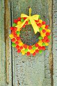 Beautiful wreath of candies hanging on old wooden door