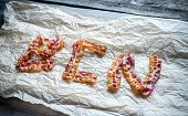 picture of bacon strips  - Fried Bacon Strips Put In Letters On The Baking Paper - JPG