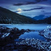 Lake Shore With Stones Near Pine Forest On Mountain At Night