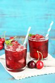 Closeup of cherry granita in glasses, on color wooden background