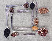 Seasonings in metal spoons on fabric background