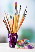 Paint brushes with paints on bright background