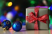 Gift box and decorations on Christmas tree lights background