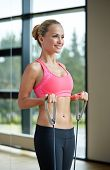 fitness, sport, people and lifestyle concept - smiling woman doing exercises with expander in gym
