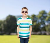 happiness, summer and people concept - smiling cute little boy in sunglasses over park background