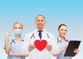 medicine, profession, teamwork and healthcare concept - international group of smiling medics or doctors holding red paper heart shape clipboard and stethoscopes over blue background