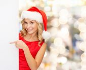 winter holidays, christmas, advertising and people concept - smiling young woman in santa helper hat with white blank billboard over lights background