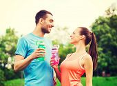 fitness, sport, friendship and lifestyle concept - smiling couple with bottles of water outdoors