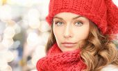 happiness, winter holidays, christmas and people concept - close up of young woman in red hat and scarf over lights background