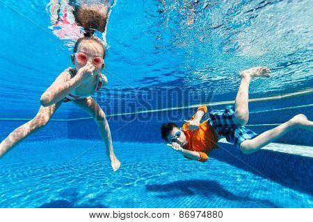Kids having some good times playing submerged in swimming pool on summer get-away