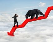 stock photo of stop fighting  - Businessman against black bear on red arrow downward trend line with sky cloudscape background - JPG