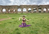 stock photo of aqueduct  - belly dancer with sword under the ancient Roman aqueduct - JPG