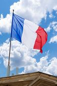 image of waving  - French flag on top of a building waving in the wind - JPG