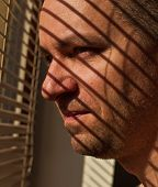 image of blind man  - Handsom man looking out a window though blinds - JPG