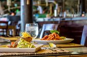 foto of pasta  - grilled salmon steak served with pasta and vegetables in a small outdoor restaurant - JPG