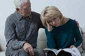 picture of wifes  - Senior man hugging upset wife having financial problems - JPG