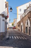 image of aqueduct  - Narrow street of Evora with remaining of a Roman aqueduct in Portugal - JPG