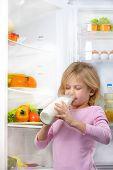 Постер, плакат: Little cute girl drinking milk near open fridge