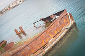 stock photo of wrecking  - Rusty wreck moored abandoned in the pier in the harbor of Cagliari Sardinia - JPG