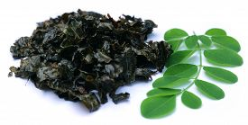 stock photo of malunggay  - Fried and green moringa leaves over white background - JPG