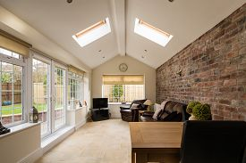 stock photo of roof-light  - Modern Sunroom or conservatory extending into the garden with a featured brick wall - JPG
