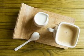 stock photo of milkman  - Coffee set on a special support of a coffee cup a spoon and a milkman - JPG