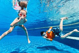 picture of little sister  - Kids having fun playing underwater in swimming pool on summer vacation - JPG