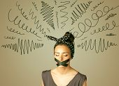 foto of taboo  - Young woman with taped mouth and curly lines around her head - JPG
