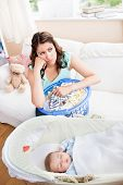 Bored Mother Waiting For Her Baby To Wake-up Sitting In The Sofa With Her Laundry Basket