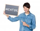 stock photo of mentoring  - Asian man finger point to chalkboard and showing a word mentor - JPG