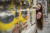 stock photo of stone house  - Two cute teen girls look out from behind the corner of a stone house - JPG
