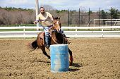 image of barrel racing  - A young man turns around a barrel and races to the finish - JPG