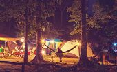 Amazing scene in night camping -girl in hammock on tents background poster