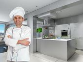 Smiling chef in a modern industrial metallic kitchen