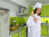 Smiling female chef in a modern green kitchen